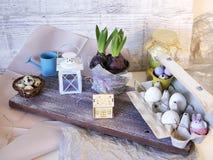 Цветочный горшок с обрабатыванными землю гиацинтами, яйцами цыпленка, яйцами триперсток, оформлением пасхи на деревянной светлой  стоковое фото