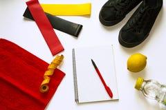 Цели спорта и плоский положенный состав от взгляда сверху на белой предпосылке Тетрадь и ручка для проверки, детандеры камедей фи стоковое фото rf