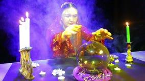 Цыганская женщина в красном платье в комнате для удачи говоря в слойках дыма читает будущее в шарике зеркала на сток-видео