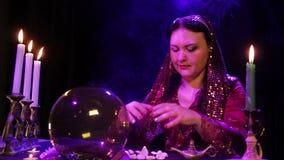 Цыган в красном платье в дыме светом горящей свечи читает будущее в шарике зеркала акции видеоматериалы