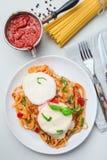 Цыпленок caprese с сыром томата и моццареллы, который служат с linguine, томатным соусом и базиликом, вертикалью, взглядом сверху стоковая фотография