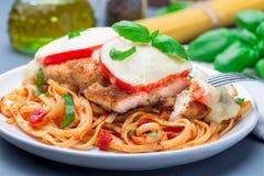 Цыпленок caprese с сыром томата и моццареллы, который служат с linguine, соусом для пасты томата и базиликом, горизонтальными, кр стоковое изображение rf
