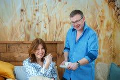 Чай утра Супруг принес его кофе чая жены к кровати стоковое фото