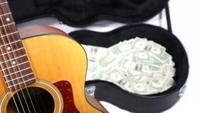 Частично акустическая гитара в фокусе, случае с деньгами из фокуса, острой глубины поля стоковое фото rf
