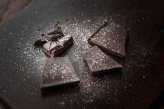 Части горького шоколада с солью моря на темной деревянной поверхности стоковые фото