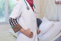 Часть тела доктора женского hijab мусульманского представляя перед камерой с ее пациентом женщины лежа на кровати за ей стоковые изображения