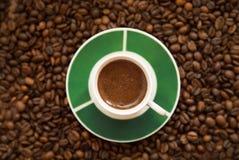 чашечка крепкого кофе. Mug of strong coffee on scattered coffee beans Stock Photography