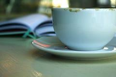 Чашка и плоская на таблице в кафе стоковое фото