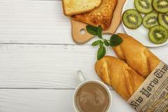Чашка кофе, свежий хлеб, тост на белой древообразной предпосылке Хлеб завтрака утра свежий с чашкой кофе Взгляд от abo стоковые фото