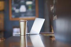 Чашка & ноутбук Thermos на таблице внутри кофейни стоковое фото