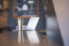 Чашка & ноутбук Thermos на таблице внутри кофейни стоковая фотография