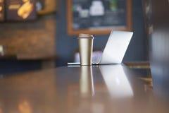 Чашка & ноутбук Thermos на таблице внутри кофейни стоковое фото rf