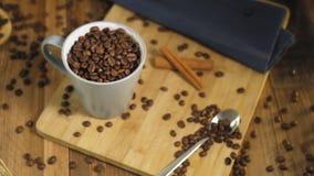 Чашка с зажаренными в духовке кофейными зернами на таблице видеоматериал