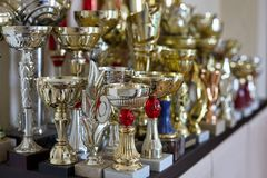 Чашки спорт, трофеи на полке, золотой и серебряный изображение принципиальной схемы 3d представило победу стоковое изображение