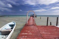 Чеканщика Caye горизонта пристани шлюпки море Белиза далекого карибское стоковые фото