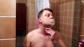 Человек бреет щеки подбородок и шею перед зеркалом видеоматериал