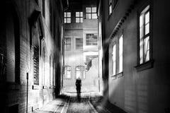 Человек бродяжничает через пугающий узкий переулок в темной ночи стоковая фотография rf