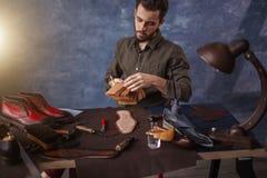 Человек выполняет восстановление старых ботинок стоковая фотография