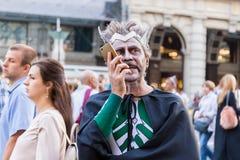 Человек в костюме масленицы говорит смартфоном стоковые изображения
