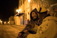 Человек 2 в традиционном морокканском djellaba идя на улицу Asilah Medina, на Атлантика побережье в Марокко кавказско стоковое изображение rf