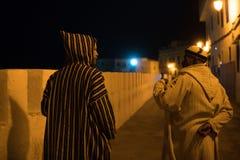 Человек 2 в традиционном морокканском djellaba идя на улицу Asilah Medina, на Атлантика побережье в Марокко кавказско стоковое изображение