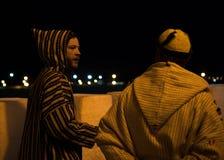 Человек 2 в традиционном морокканском djellaba идя на улицу Asilah Medina, на Атлантика побережье в Марокко кавказско стоковые изображения