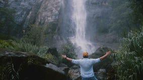 Человек заднего взгляда возбужденный молодой туристский с моментами оружий широкими открытыми наслаждаясь эпичными свободы на вод акции видеоматериалы