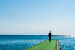 Человек идет к зеленой пристани нырнуть стоковые фото