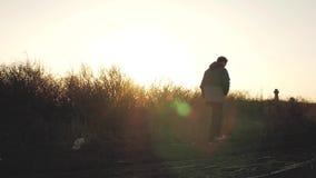 Человек идет на заход солнца около каменных крестов видеоматериал