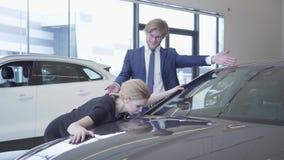 Человек и женщина в официальной носке как раз купили автомобиль в современном мотор-шоу Дама будет в восторге и счастливый, она о видеоматериал