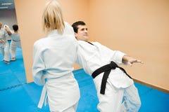Человек и женщина воюя на тренировке айкидо в школе боевых искусств стоковые фото