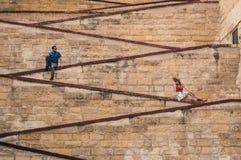 Человек и женщина сидя на городских стенах стоковое изображение rf