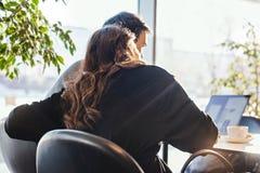 Человек и женщина работая перед ноутбуком с пустым белым экраном и обнимать стоковые фото