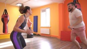 Человек и подогрев девушки в спортзале перед тренировкой в спорт кладя в коробку, замедленным движением, стуком-вверх видеоматериал