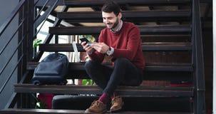 Человек менеджера офиса в середине залы офиса на лестницах используя его смартфон для того чтобы сделать онлайн сделку он принима видеоматериал