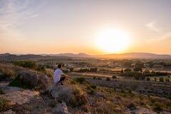 Человек наблюдая заход солнца в горе стоковые фото