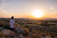 Человек наблюдая заход солнца в горе стоковая фотография