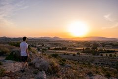 Человек наблюдая заход солнца в горе стоковое изображение rf