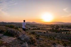 Человек наблюдая заход солнца в горе стоковое фото rf