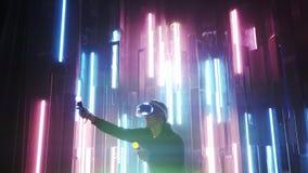 Человек нося шлемофон VR и двигая руки в неоновом свете видеоматериал