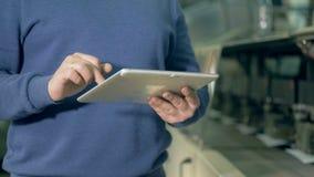 Человек печатает на планшете на офисе печати, конце вверх сток-видео