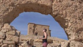 Человек путешественника используя его смартфон для навигации GPS в каменной дуге старых остатков в Марокко Путешествовать в Ourza видеоматериал