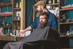 Человек при борода покрытая при черная накидка ждать пока ранг клипера парикмахера изменяя Клиент битника получая стрижку стоковые изображения