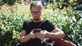 Человек просматривает социальные сети его смартфоном outdoors в парке, сидит на стенде видеоматериал