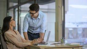 Человек помогая к его азиатскому женскому коллеге заполняет в нежном применении, сыгранности акции видеоматериалы