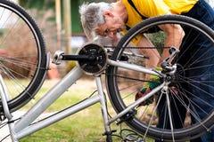 Человек поддерживая его велосипед на новый сезон стоковая фотография