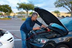 Человек давая толчек автомобиль с соединительными кабелями стоковые изображения