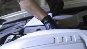 Человек делая обслуживание проверяя уровень масла после изменения масла в двигателе автомобиля внутри помещения на желтой предпос видеоматериал