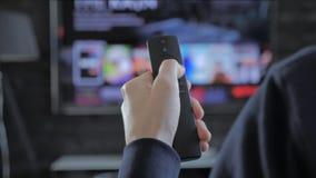 Человек держа дистанционное управление и ища для течь средства массовой информации для игры акции видеоматериалы