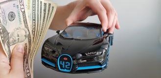 Человек держит в его руке в игрушке металла автомобиля Bugatti Chiron воздуха черной пока другой человек дает ему пачку денег стоковая фотография rf